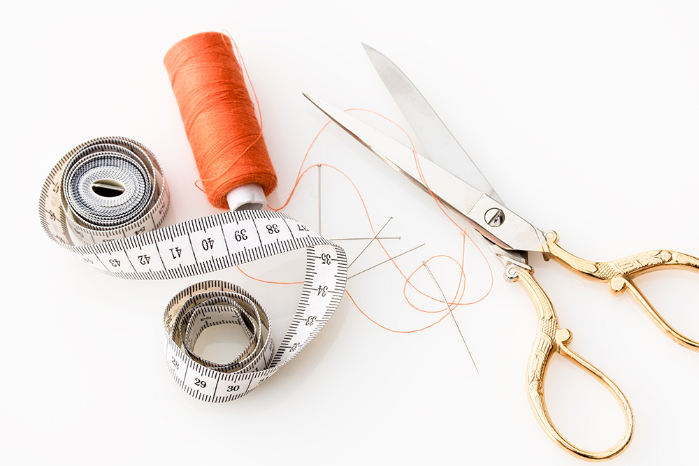 sewing materials scissors, tape measure and thread images